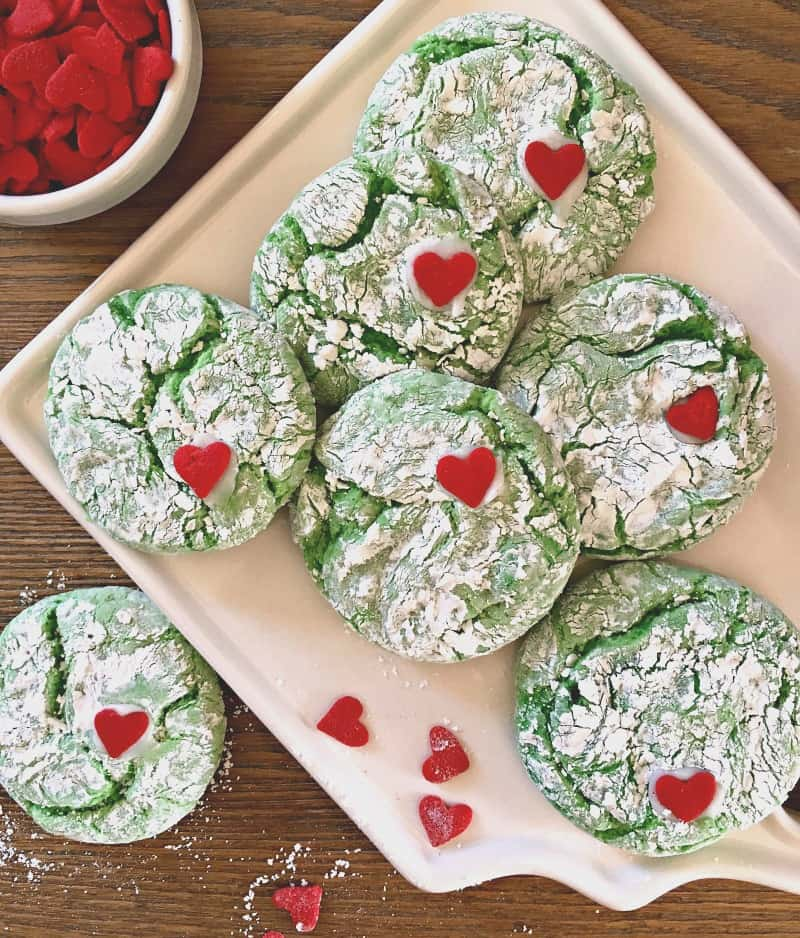 grinch cookies ~ overhead photo of green and white crinkle cookies with a small red heart