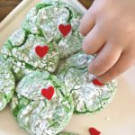 grinch cookies with cake mix ~ overhead photo of green crinkle cookies with a red heart and toddler hand reaching for a cookie
