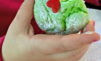 grinch cookies recipe ~ green crinkle cookie with red heart held by toddler hand and a bite taken out of it.