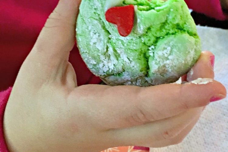 toddler hand holding cookie with bite taken out of it
