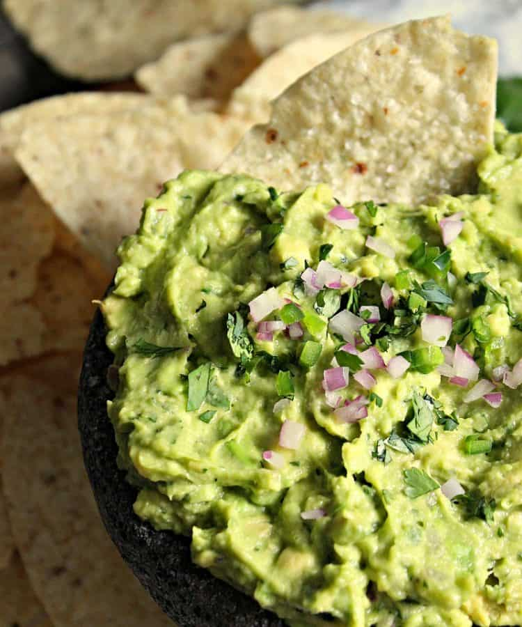 bowl of guacamole garnished with minced red onion surrounded by tortilla chips
