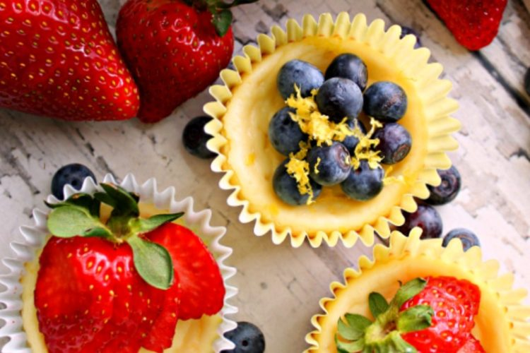 overhead view of mini cheesecakes topped with fresh fruit