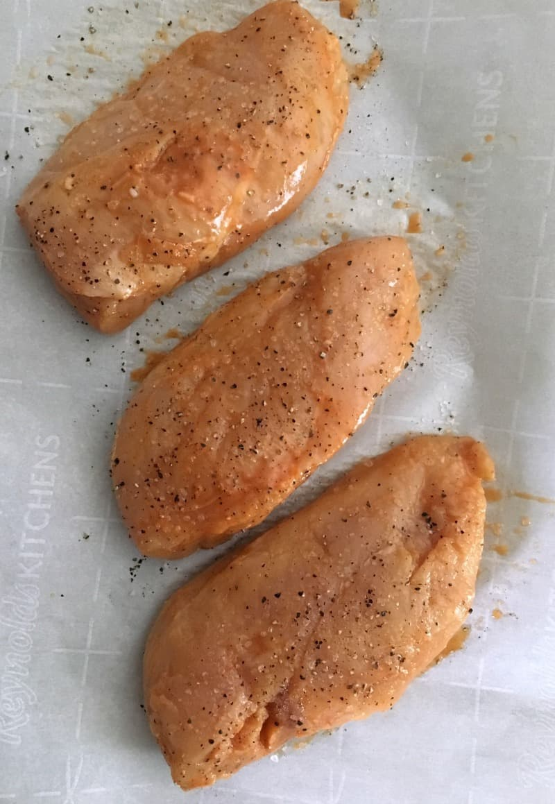raw boneless chickne breasts seasoned with salt and pepper before grilling
