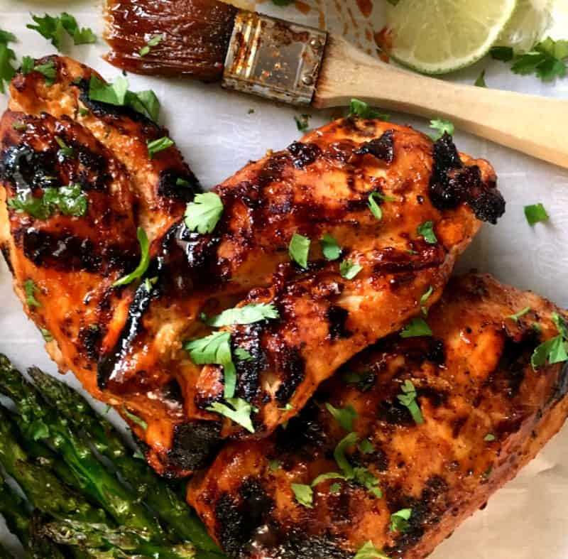 grilled chicken with honey sriracha glaze shown with basting brush, sliced lime and grilled asparagus
