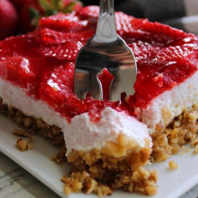 piece of strawberry pretzel jello on white plate with fork slicing into it