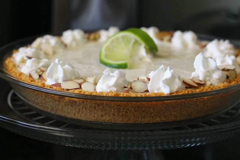 side view of finished pie dotted with shipped cream and garnished with lime slice