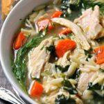 lemon chicken orzo rice ~ overhead shot of soup with pieces of chicken, carrots, orzo and spinach.