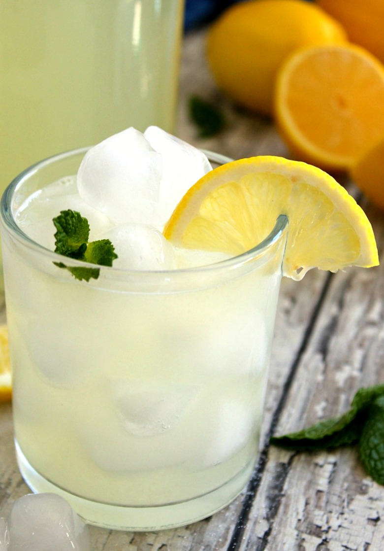 clear glass with lemonade garnished with mint sprg and lemon slice