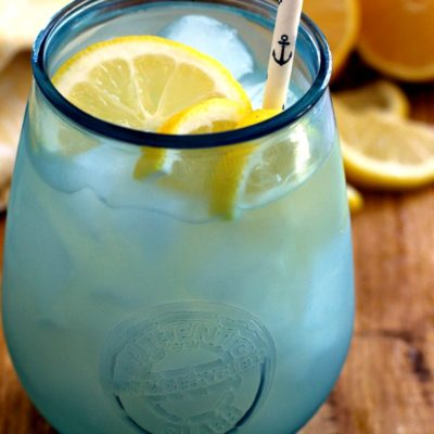homemade lemonade in icy blue glass with sliced lemons