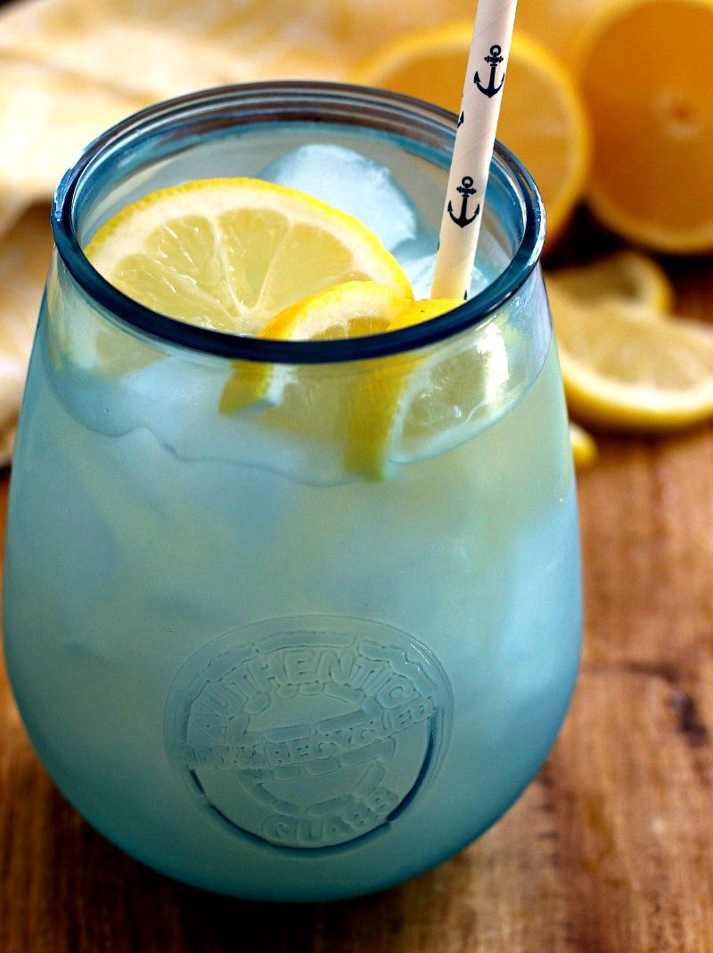 homemade lemonade in icy blue glass with sliced lemons