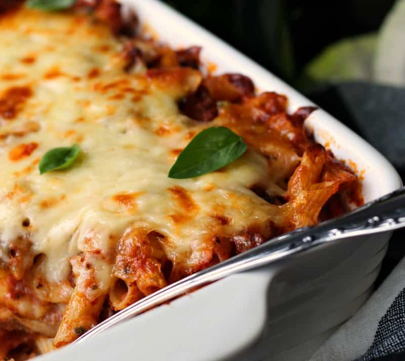 mostaccioli baked in white casserole dish topped with melted cheese