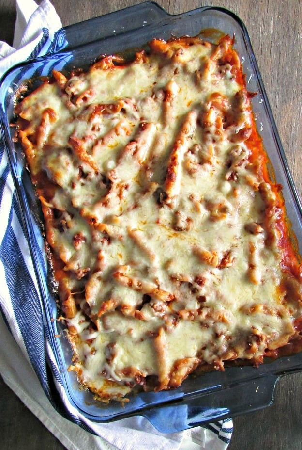 overhead view of mostaccioli with melted cheese in blue casserole dish.