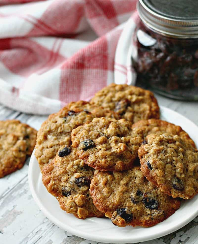 white plate of oatmeal raisin cookies with jar of raisins in the background