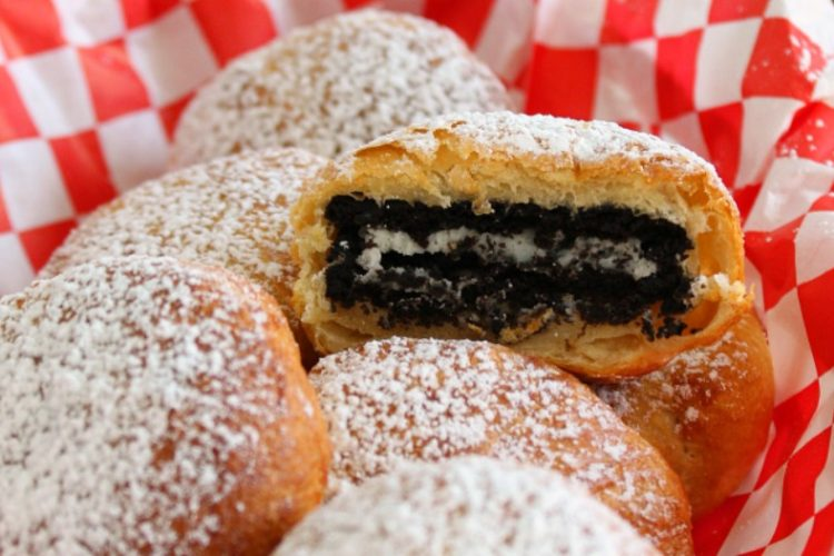 fried oreos in a red basket with one oreo cut in half showing the center