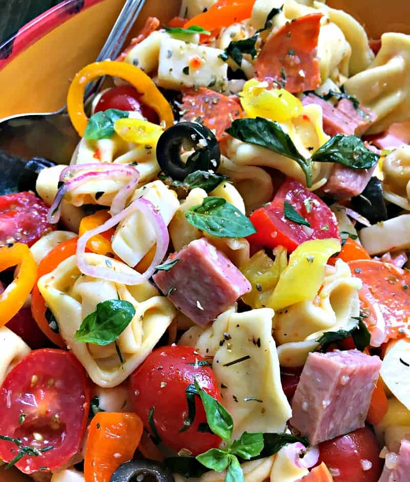 bowl of italian pasta salad in bright colored bowl, vibrant chopped vegetables and tortellini