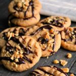 peanut butter cookies on white plate drizzled with chocolate and peanuts