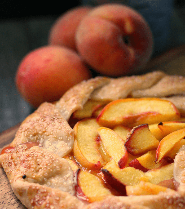 peach galette recipe ~ pre cut galette with whole peaches in background