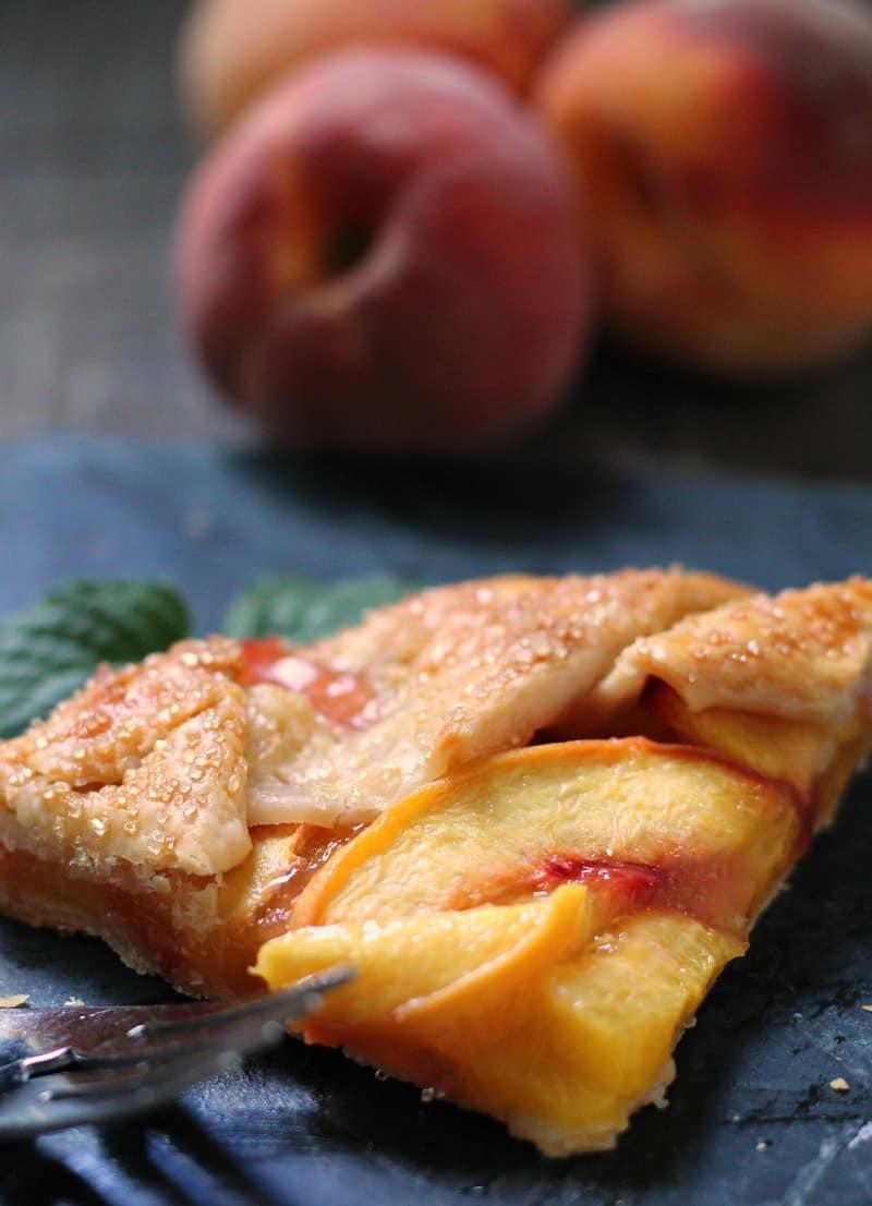 peach galette recipe ~ slice of galette with fresh peach in background