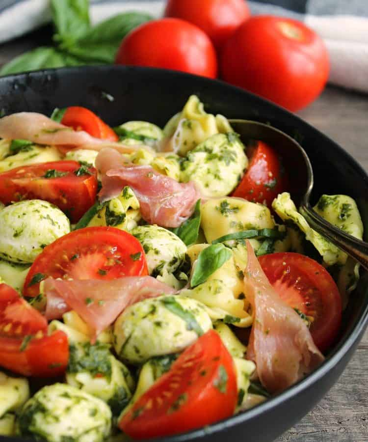 overhead view pesto tortellini salad with sliced tomatoes and prosciutto