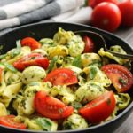 tortellini, sliced tomatoes and mozzarella balls tossed in pesto
