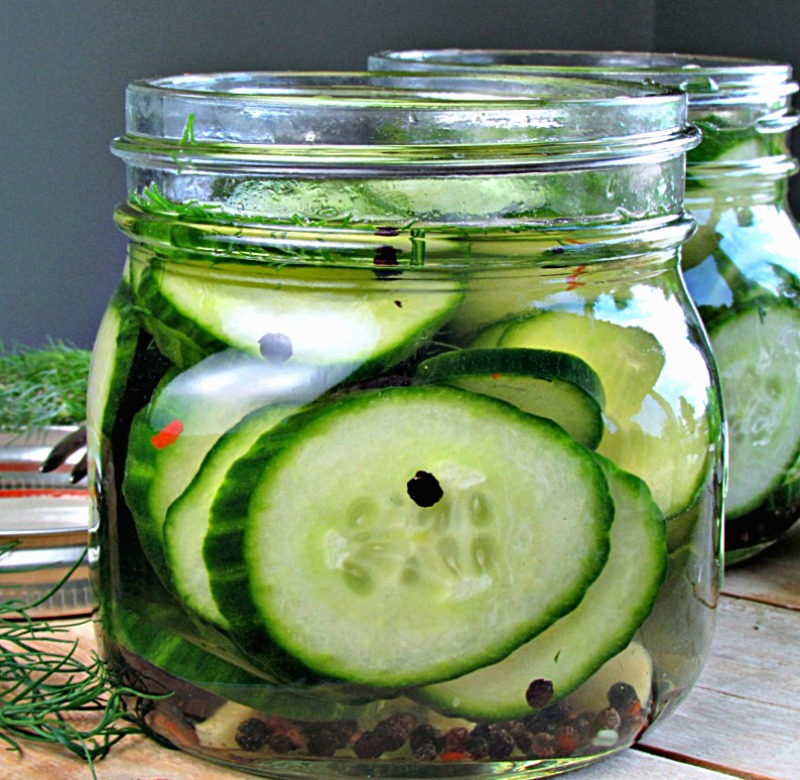 side view of dill pickles in jar with peppercorns floating