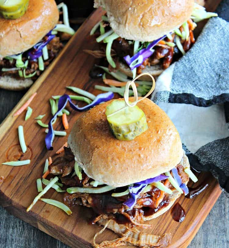 slow cooker beer braised pulled pork ~ 3 pulled pork sliders topped with confetti slaw and a dill pickle disc.