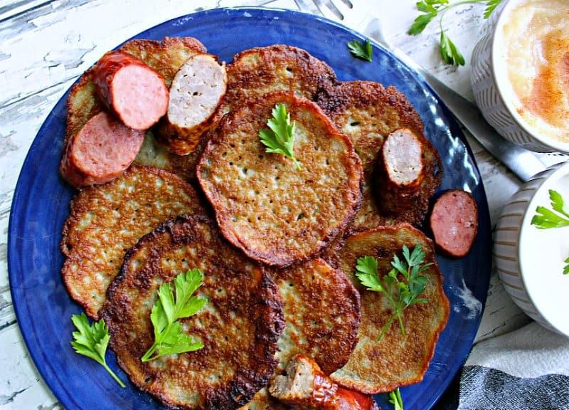 blue plate with golden potato pancakes and kielbasa