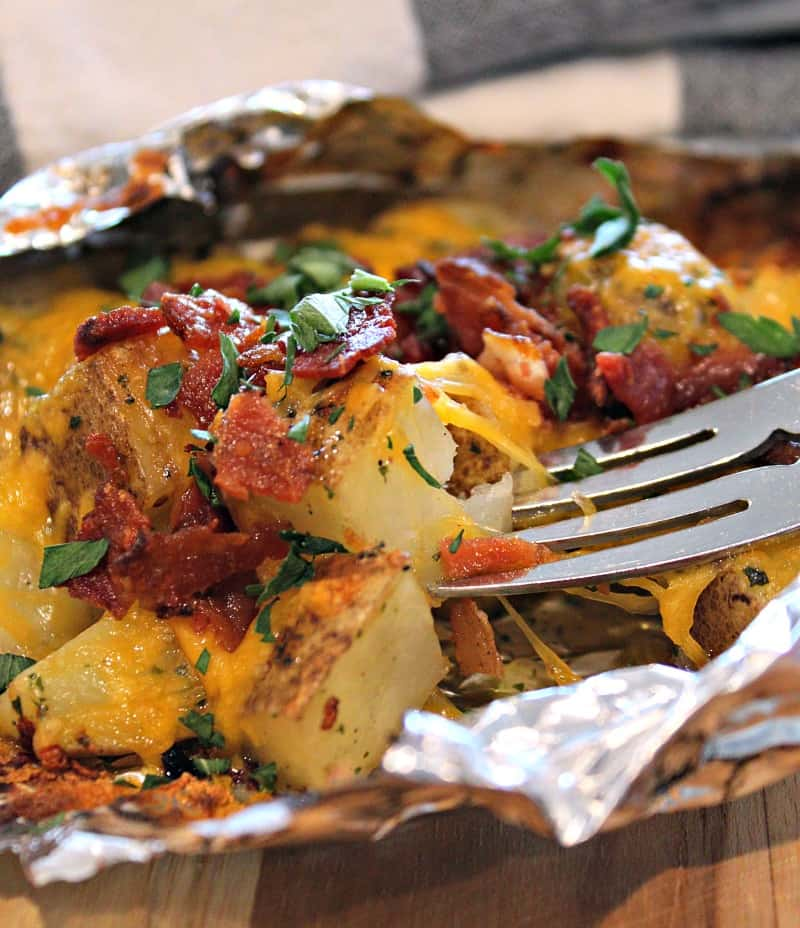 diced potatoes in open foil pack topped with melted cheese, bacon and chopped parsley