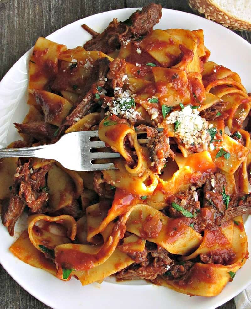 white plate with pasta and shredded beef