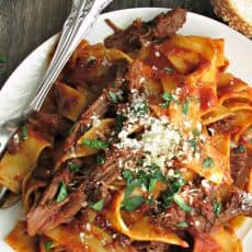 plate of beef ragu with pasta and grated parmesan
