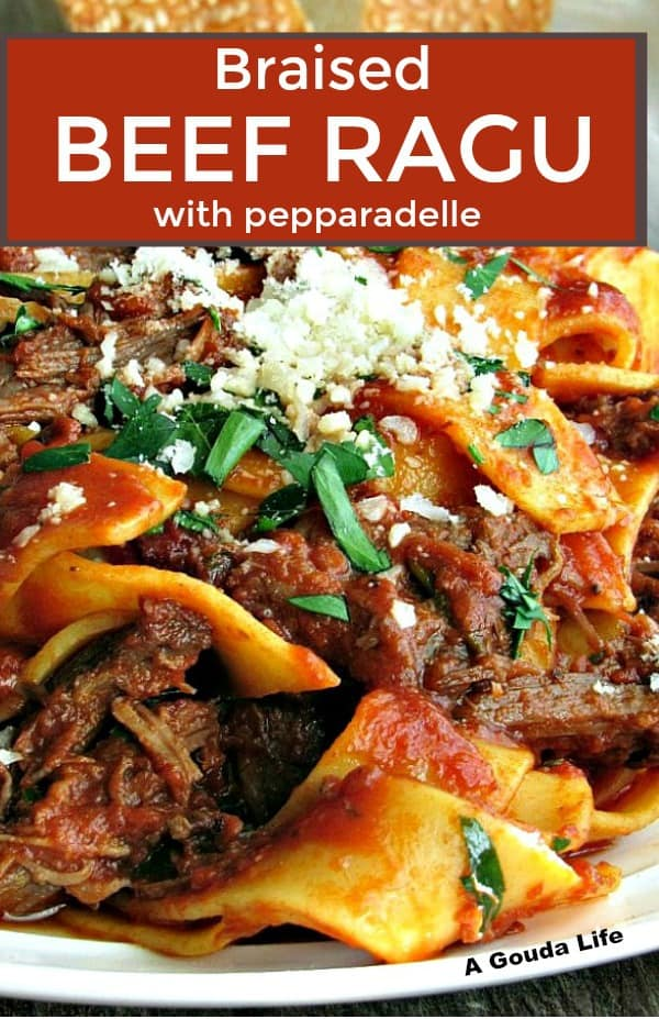 braised beef ragu ~ pin for pinterest ~ close up of shredded beef in tomato sauce blended with pappardelle and topped with grated parmesan cheese.