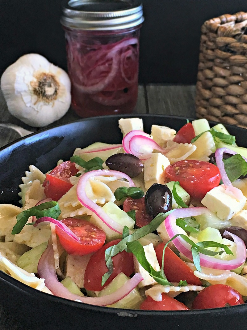 pickled red onions ~ bowl of greek pasta salad with pickled red onions, olives, feta, tomatoes and fresh herbs