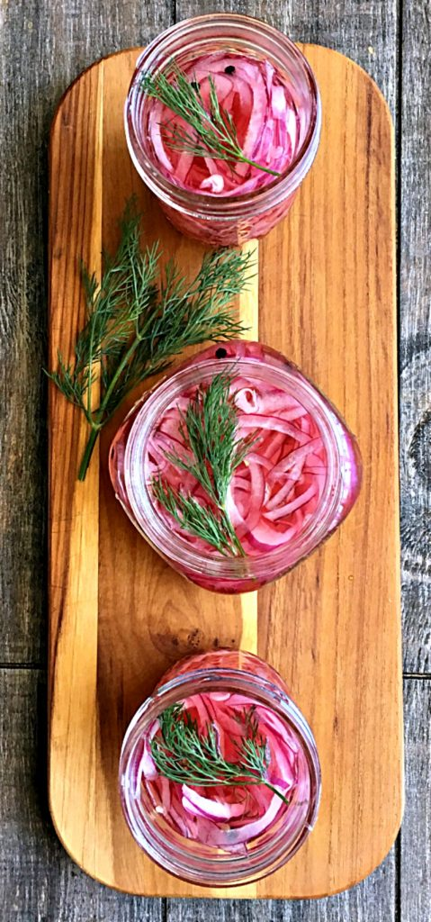 pickled red onions ~ overhead view of 3 jars with sprigs of dill on top