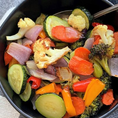 overhead view - black bowl filled with bright colored roasted vegetables