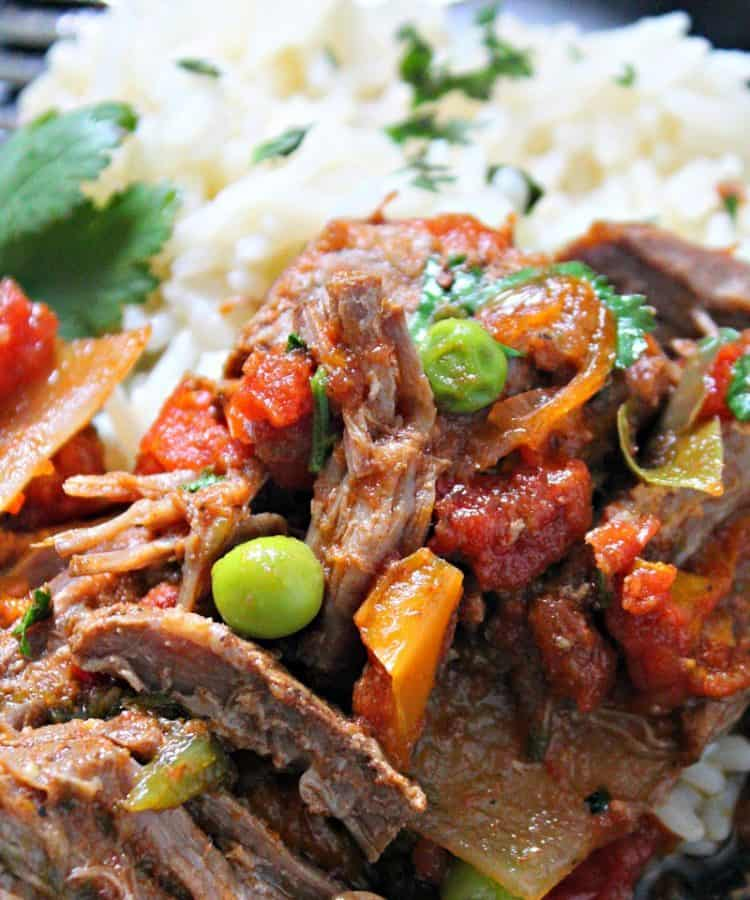 slow cooker ropa vieja - serve on a plate with white rice and black beans