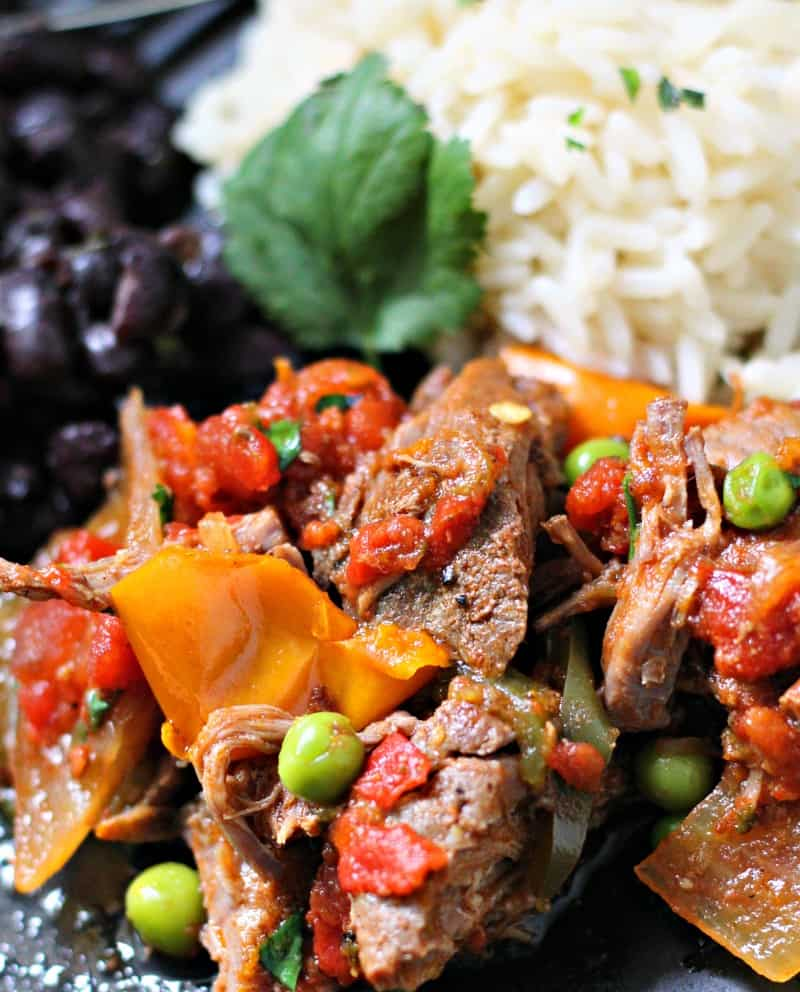 slow cooker ropa vieja shown on a plate with white rice and black beans