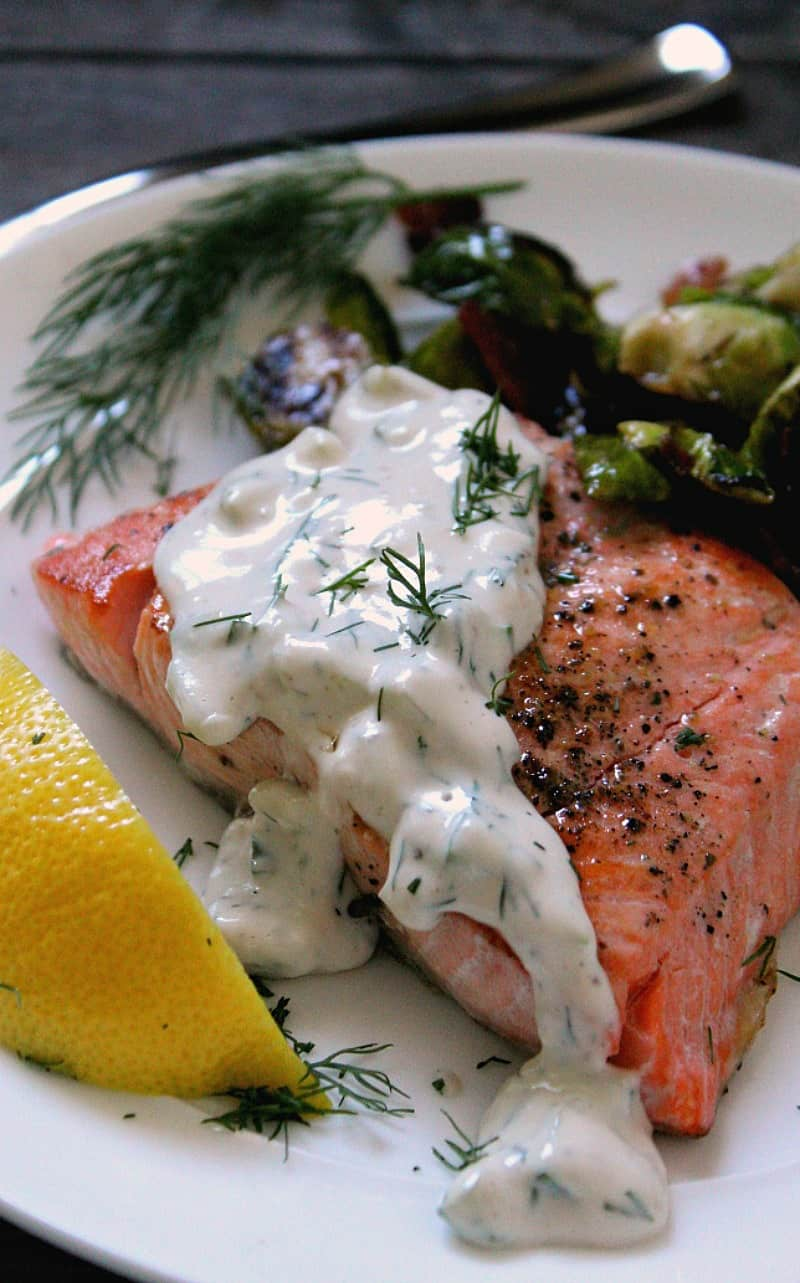 salmon filet topped with creamy sauce and side of brussels sprouts