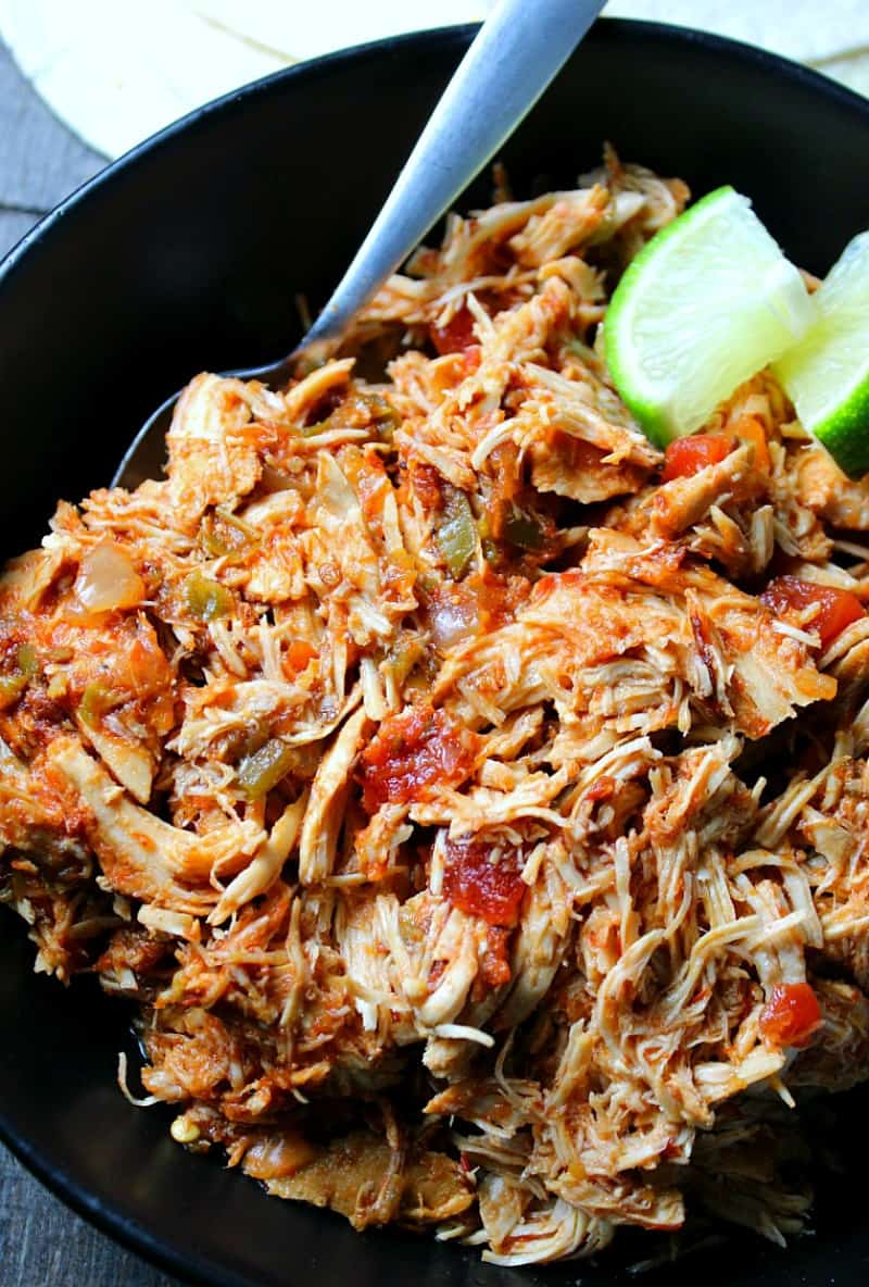 slow cooker salsa chicken ~ bowl of shredded salsa chicken garnished with lime wedges.