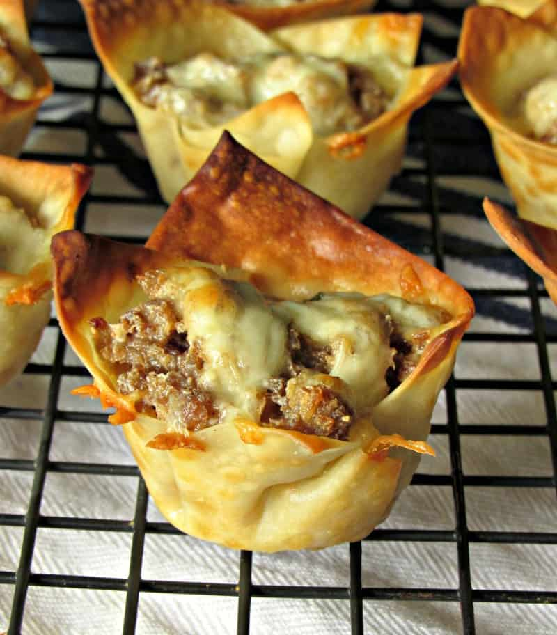 bite size wonton cups filled with ground sausage and topped with cheese