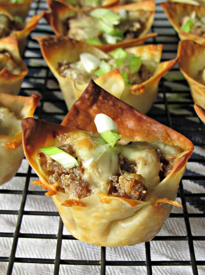mini wonton cups filled with sausage topped with sliced green onions
