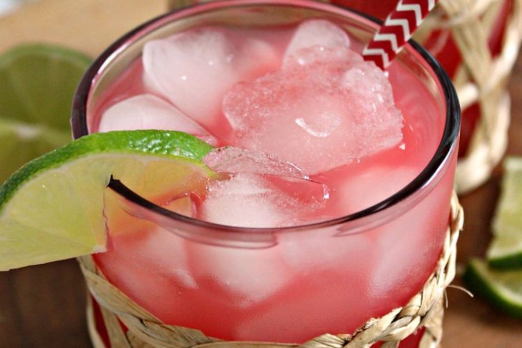 clear glass filled with ice and pink sea breeze cocktail