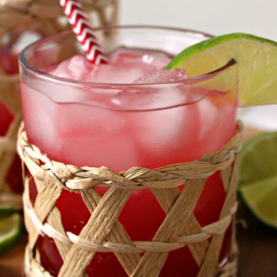 clear glass filled with pink Sea Breeze cocktail, garnished with lime slice