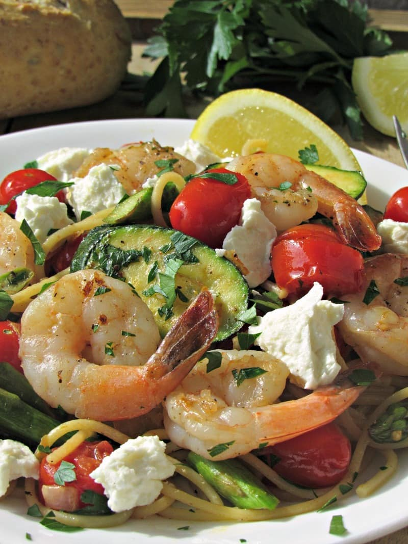 White plate with shrimp pasta primavera garnished with lemon wedge