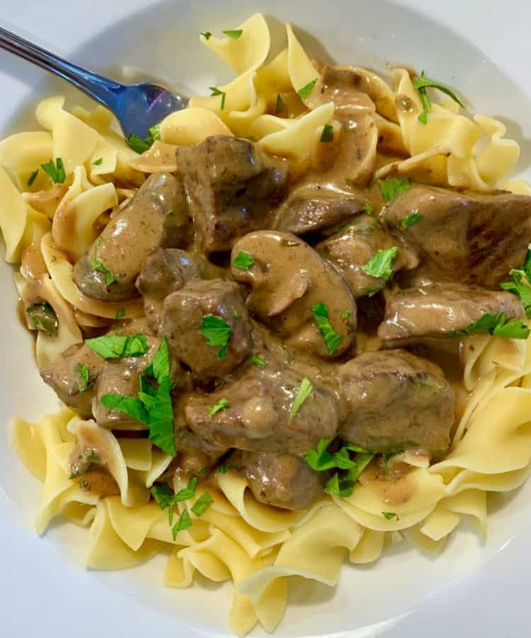 white plate with egg noodles topped with beef stroganoff