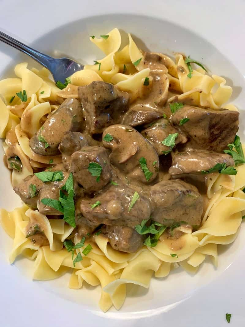 beef stroganoff over egg noodles in white bowl garnished with chopped parsley