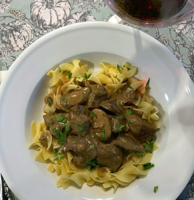 white bowl of beef stroganoff served with red winw