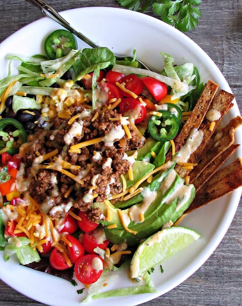 Healthy Taco Salad ~ greens + chipotle seasoned ground meat, beans, avocado, corn, tomatoes & cheese + a 5 ingredient salsa verde Greek yogurt dressing.