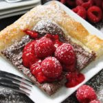 easy chocolate raspberry tart ~ light rustic chocolate raspberry tart ~ golden puffed pastry topped with Nutella, homemade raspberry sauce, fresh raspberries dusted with confectioner's sugar.