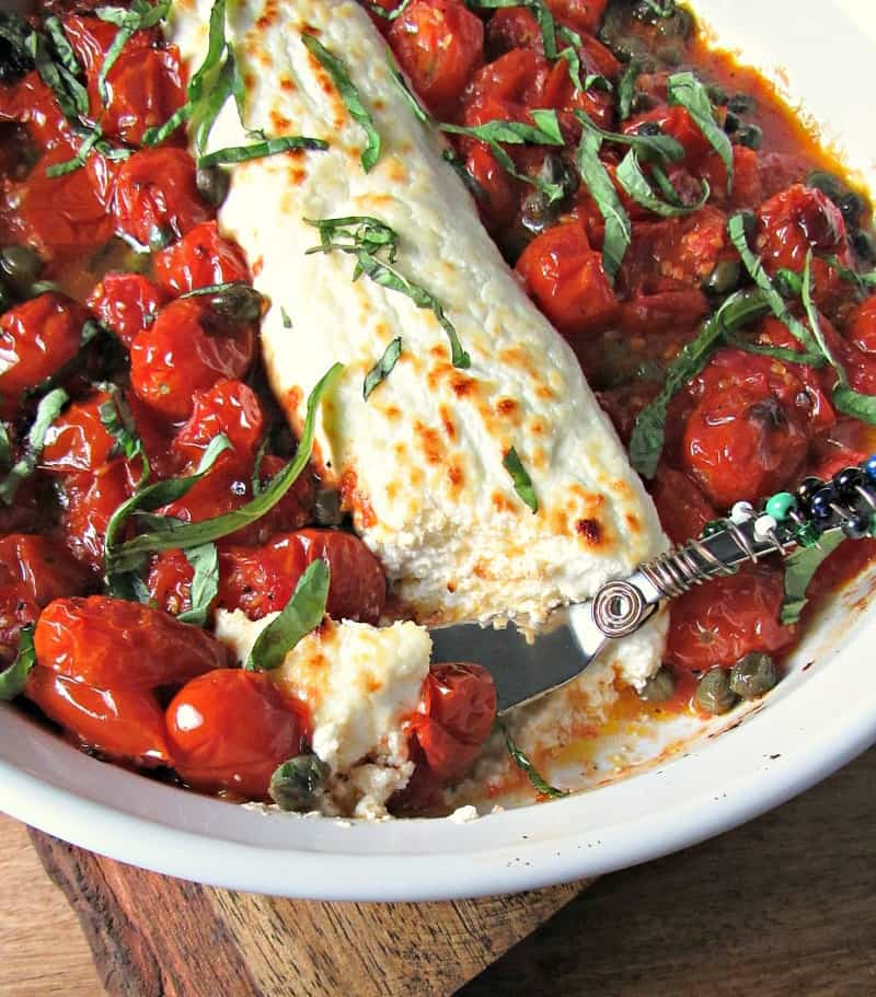 Tomato Caper Goat Cheese Appetizer ~ burst tomatoes, garlic and capers nestled around tangy goat cheese and broiled until golden. Serve with toasted bread.