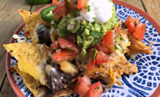 Ultimate Chicken Nachos ~ the ideal crowd-pleaser. Tortilla chips, chicken, refried black beans, lots of cheese, jalapeno, avocado, salsa & sour cream. Ole!